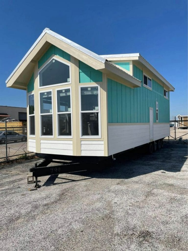 Teal and white siding with cream trim on tiny house