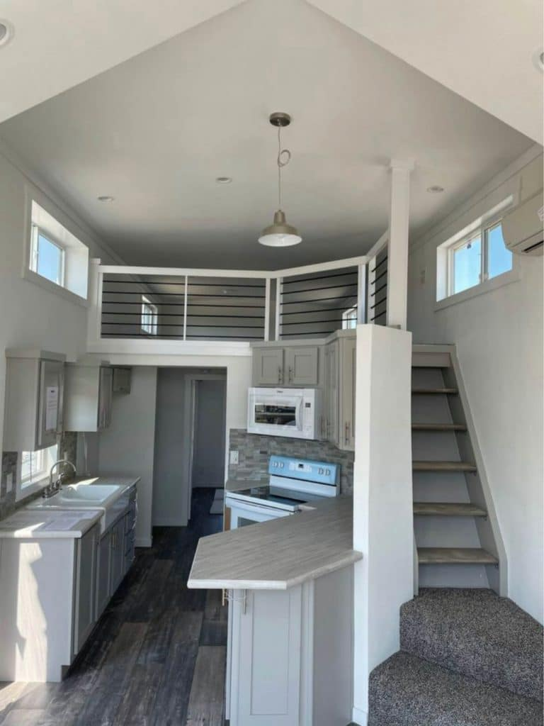 View up to tiny house loft with stairs behind kitchen