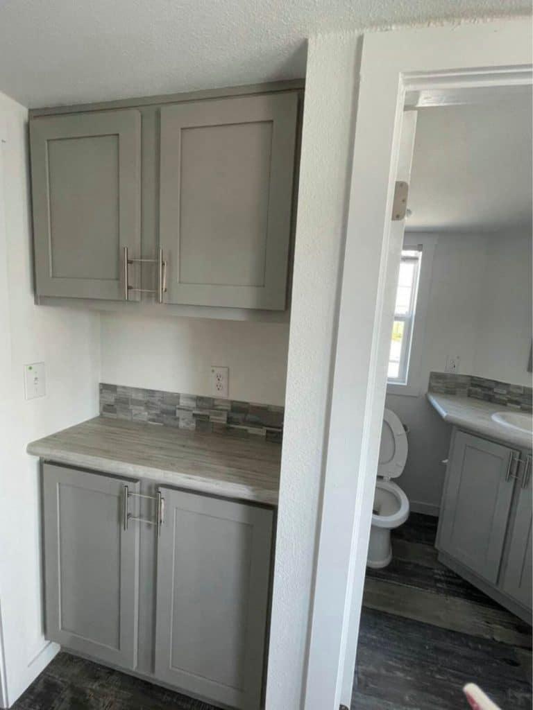Gray cabinets with small open space between next to bathroom door