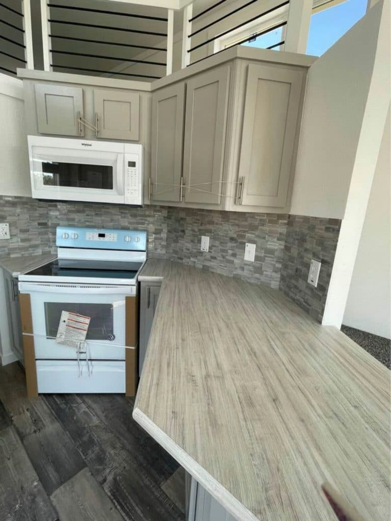 Corner stove with microwave in gray kitchen cabinets