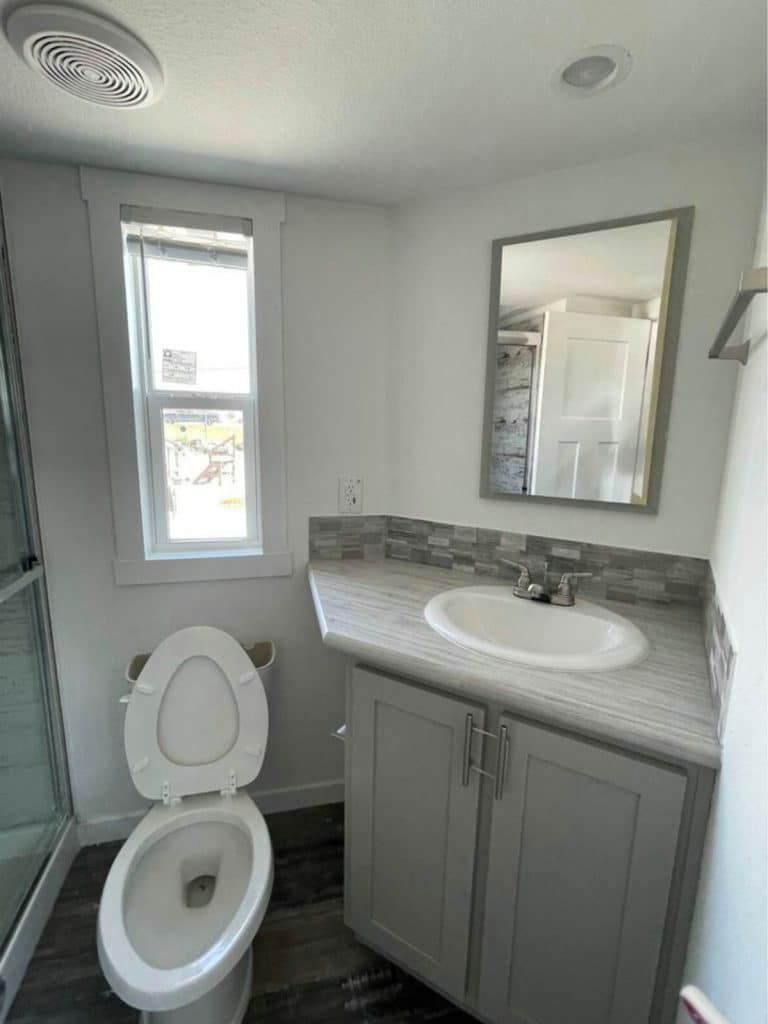 Corner sink in gray cabinet with white toilet and lid open