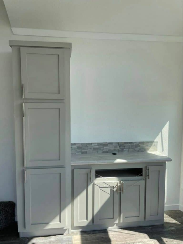 Gray cabinet and shelf for entertainment center along white wall