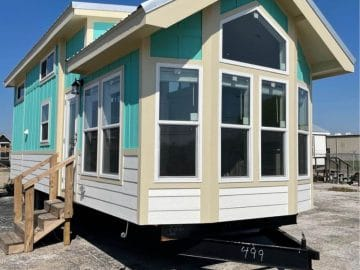 Tiny home with teal and cream siding on lot