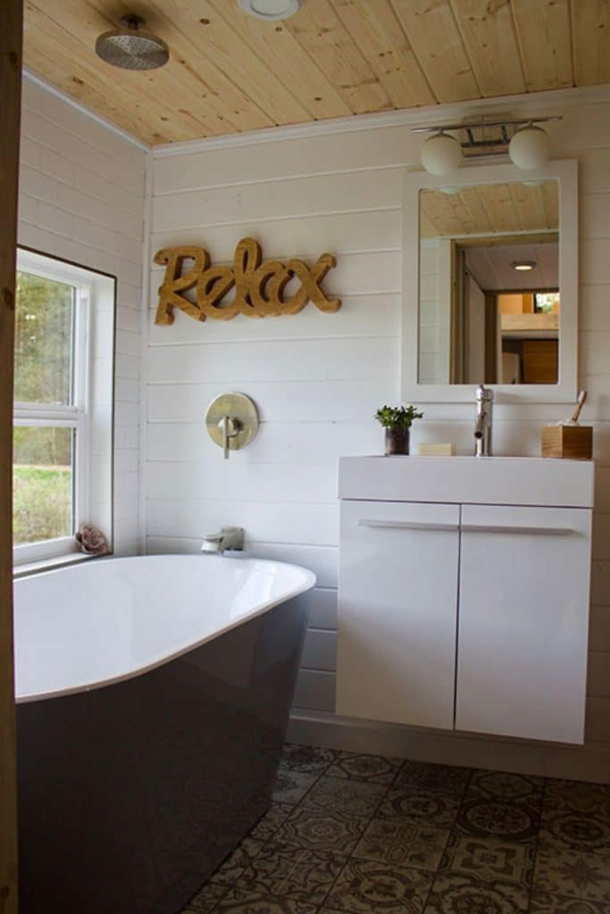White and blue soaking tub in bathroom with relax sign above