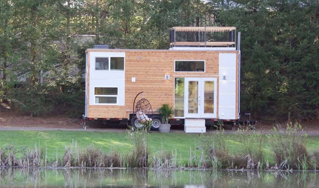 Brown tiny house by pond with white trim