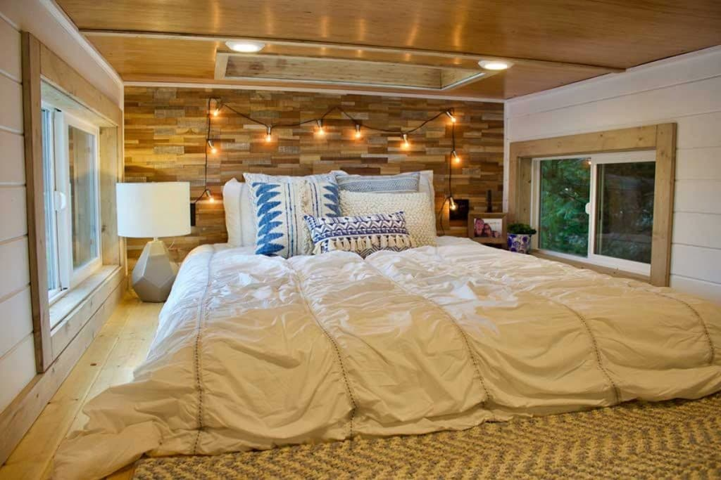 White bedding on king bed in loft with floating lights