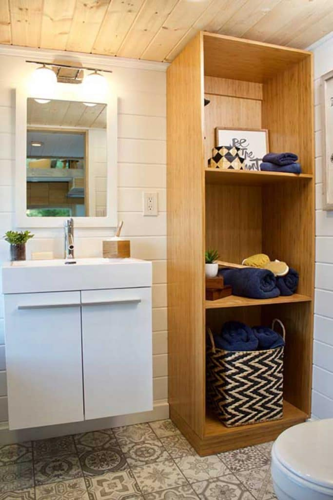 White vanity next to wooden shelves