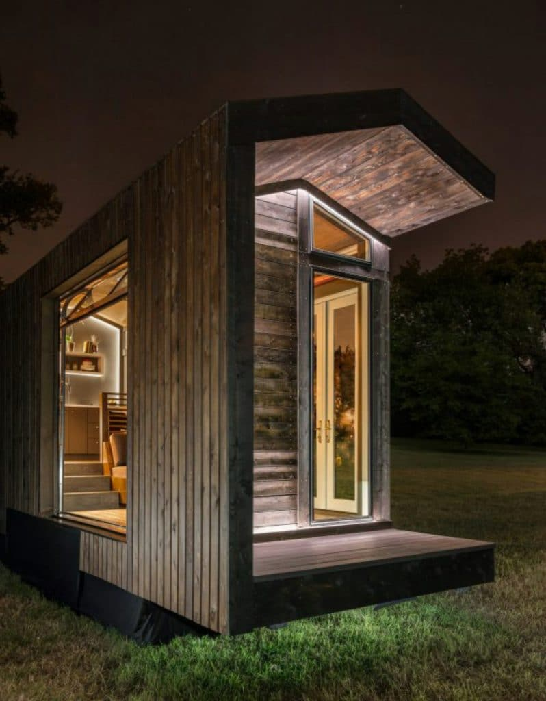 Dark wood tiny house with glass front at night