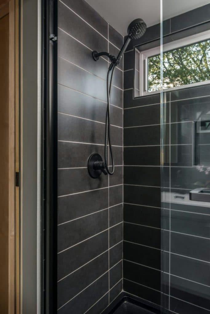 Dark gray tile in shower with glass door