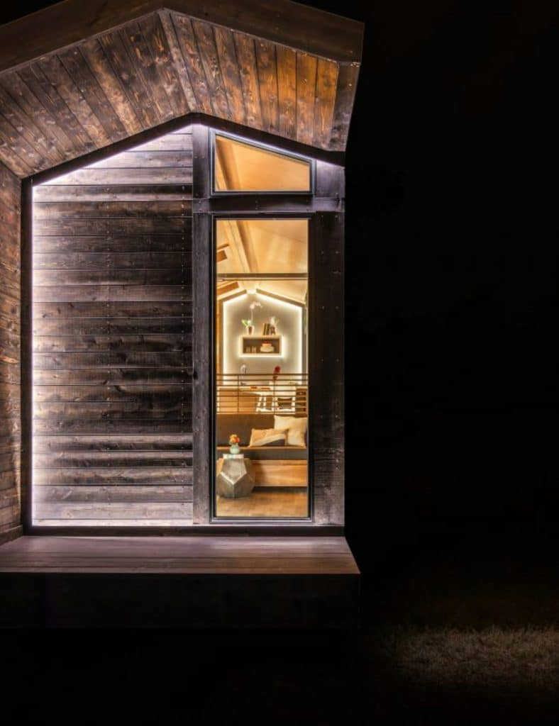 View into tiny house through window from outside at night