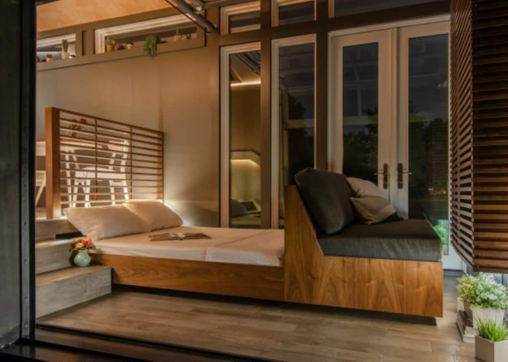 Hideaway bed open in living room with wooden base and white sheets
