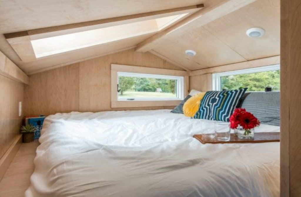 King sized bed in loft with light wood walls and sunlight