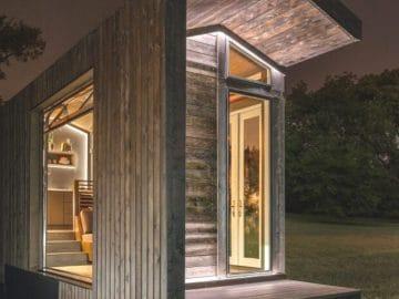 Dark wood tiny house with large windows at night