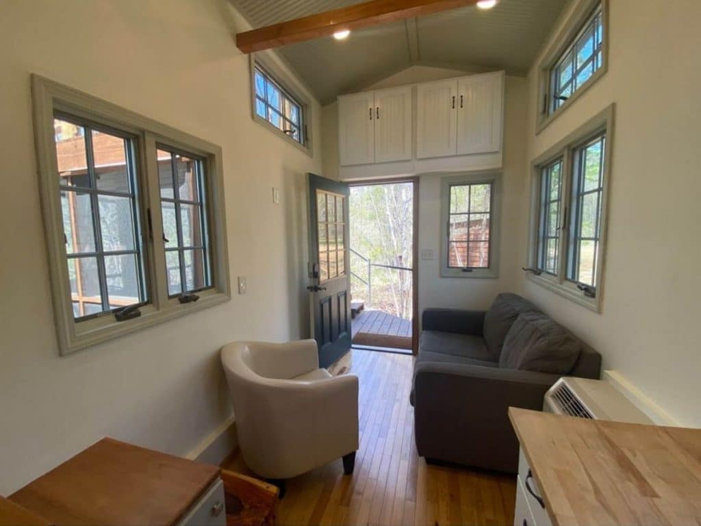 Inside of tiny house with white walls and blue sofa