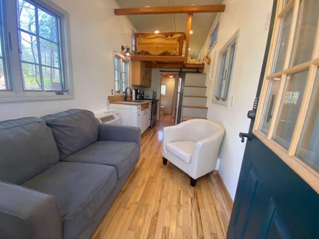 Blue sofa on one side of tiny home with white chair in background