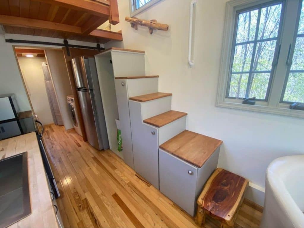 Stairs leading to loft with gray cabinets underneath
