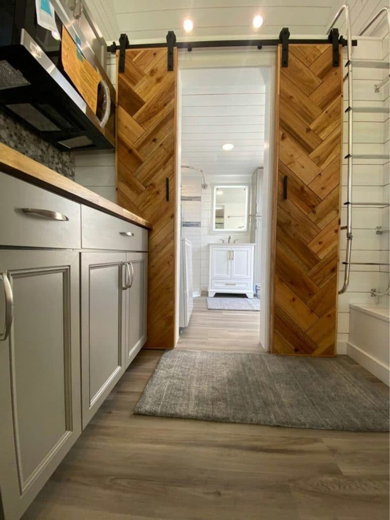 Chevron wood barn doors leading to bathroom