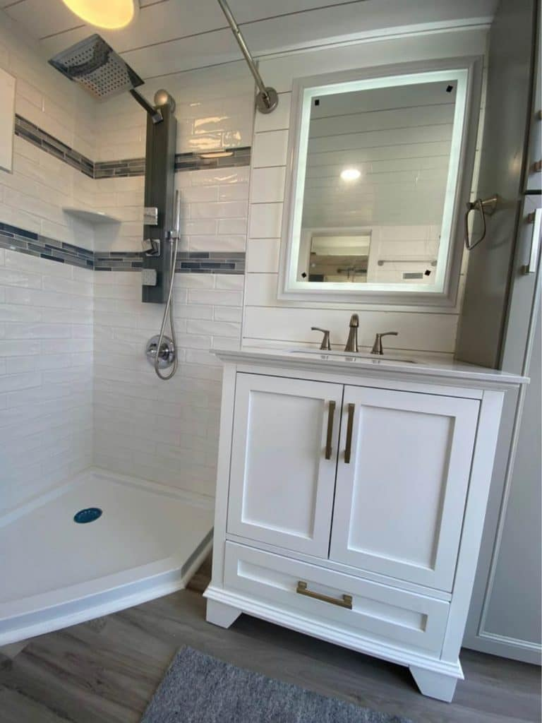 White vanity next to corner shower