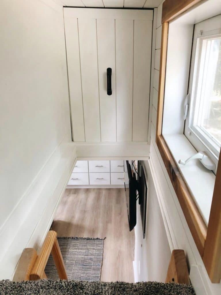 Storage cabinet above ladder to loft