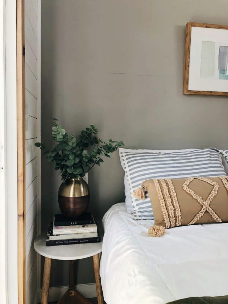 Bedside table next to striped pillows
