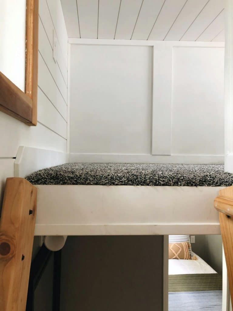 Ladder up to loft with white walls and gray carpet
