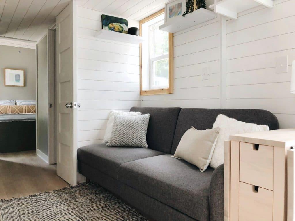 Grey sofa with white pillows and white shiplap walls