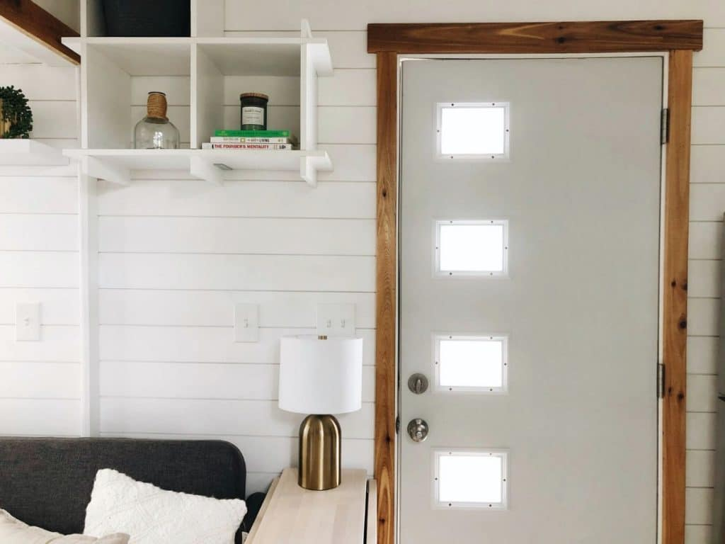 Inside door with white shiplap walls by lamp