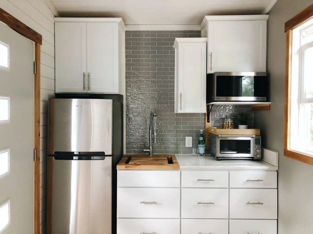 Tiny home kitchen with white cabinets