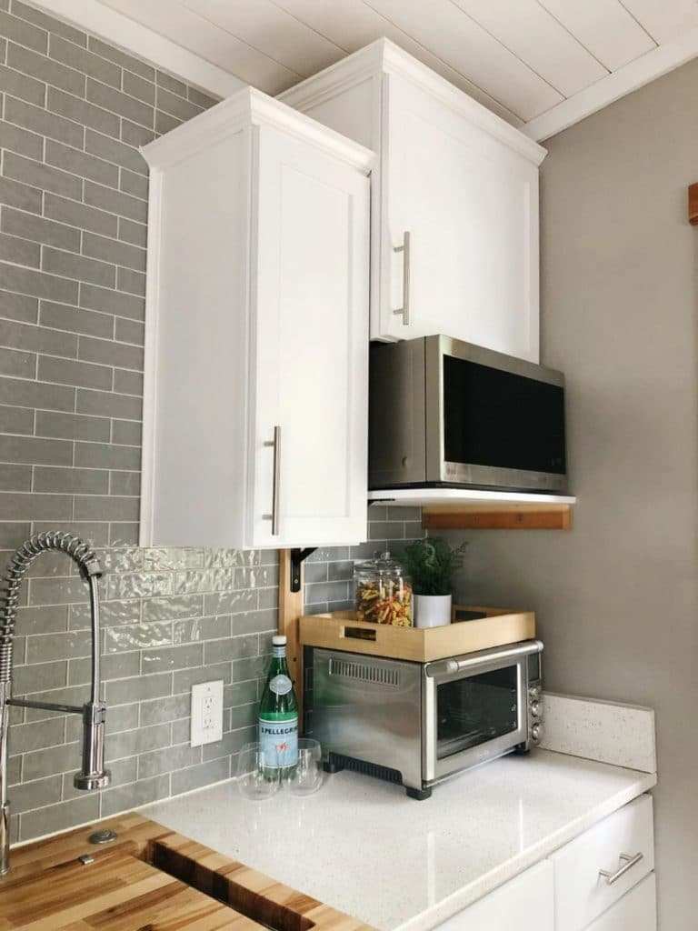 White tall cabinets in kitchen with gray tile background