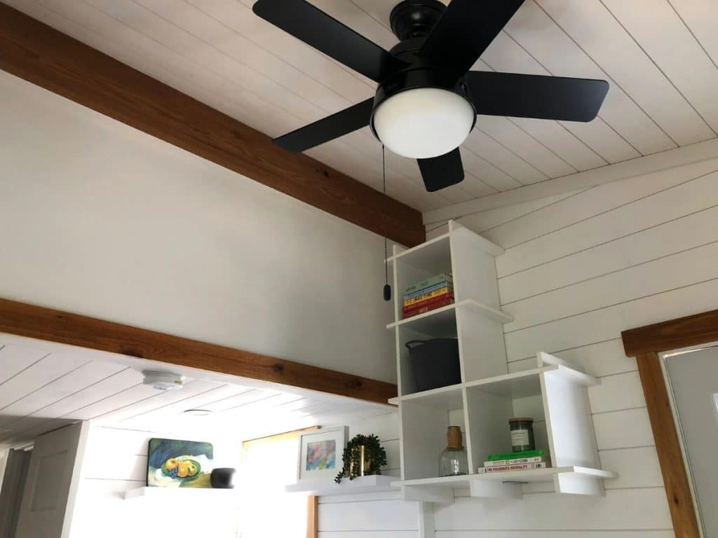 Ceiling fan in living room with open shelving on wall