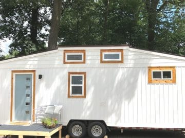 White tiny home with blue front door and orange trim