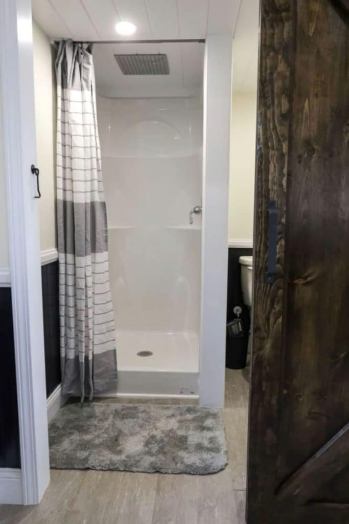 White shower stall with gray rug and striped shower curtain