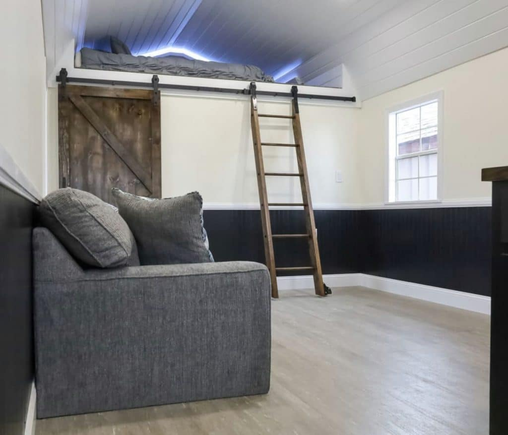 Blue sofa against wall with wood ladder leading to loft