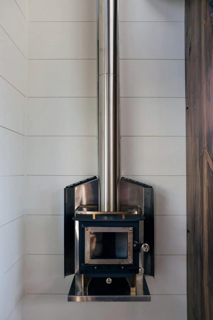 Chrome wood stove hanging aginast white shiplap
