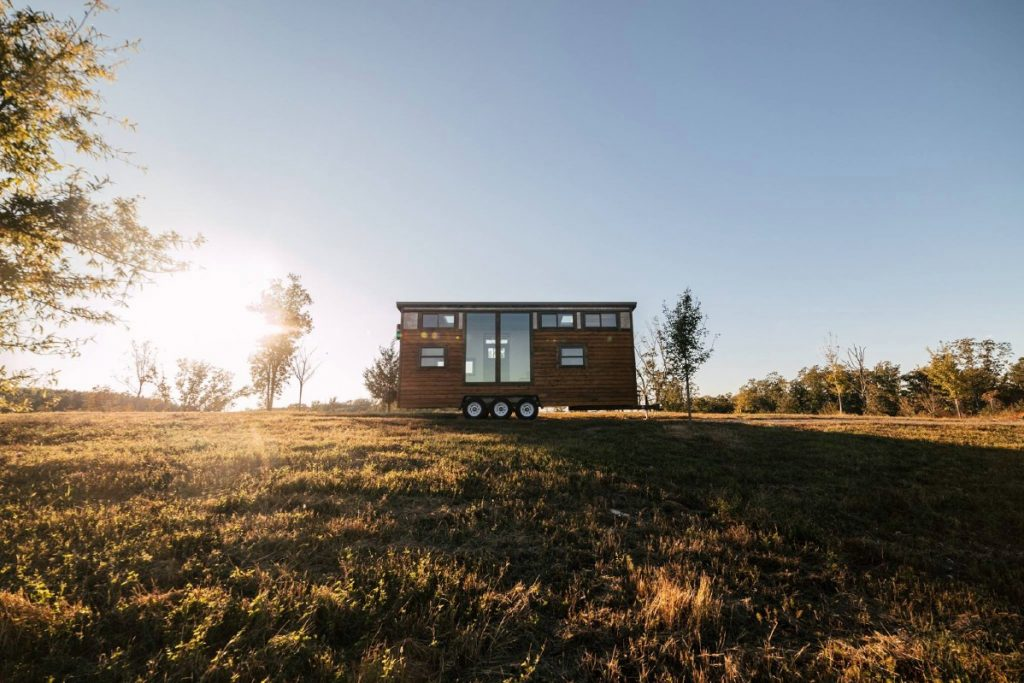 TIny house sitting on hill with sunset behind it