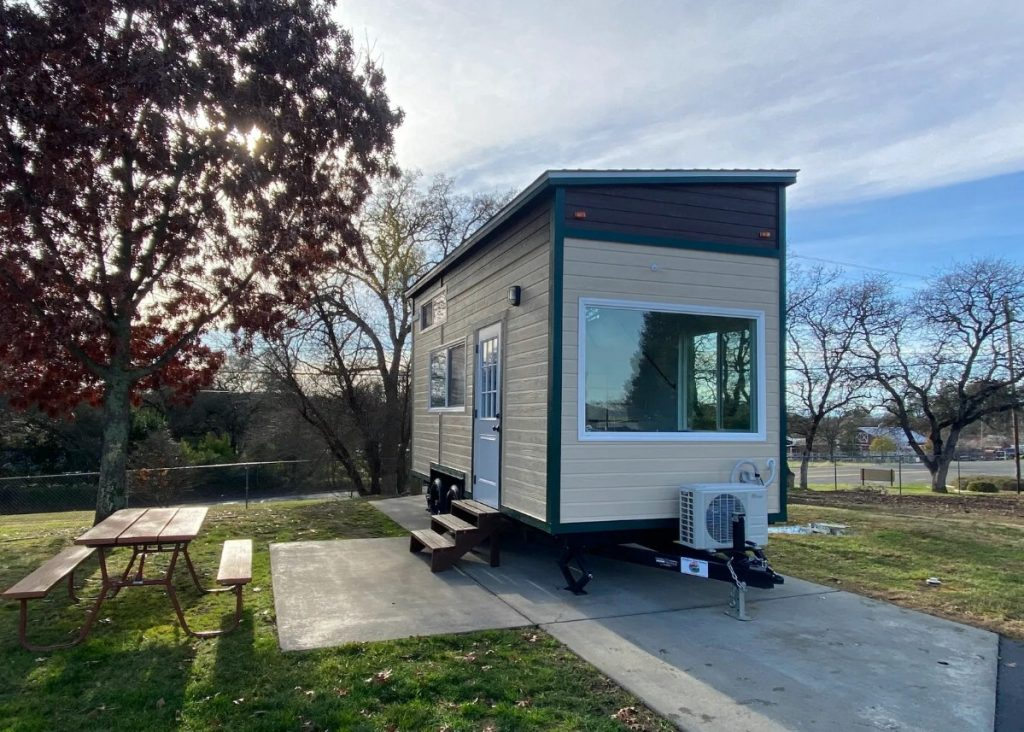 End of tiny house with large window above air conditioner