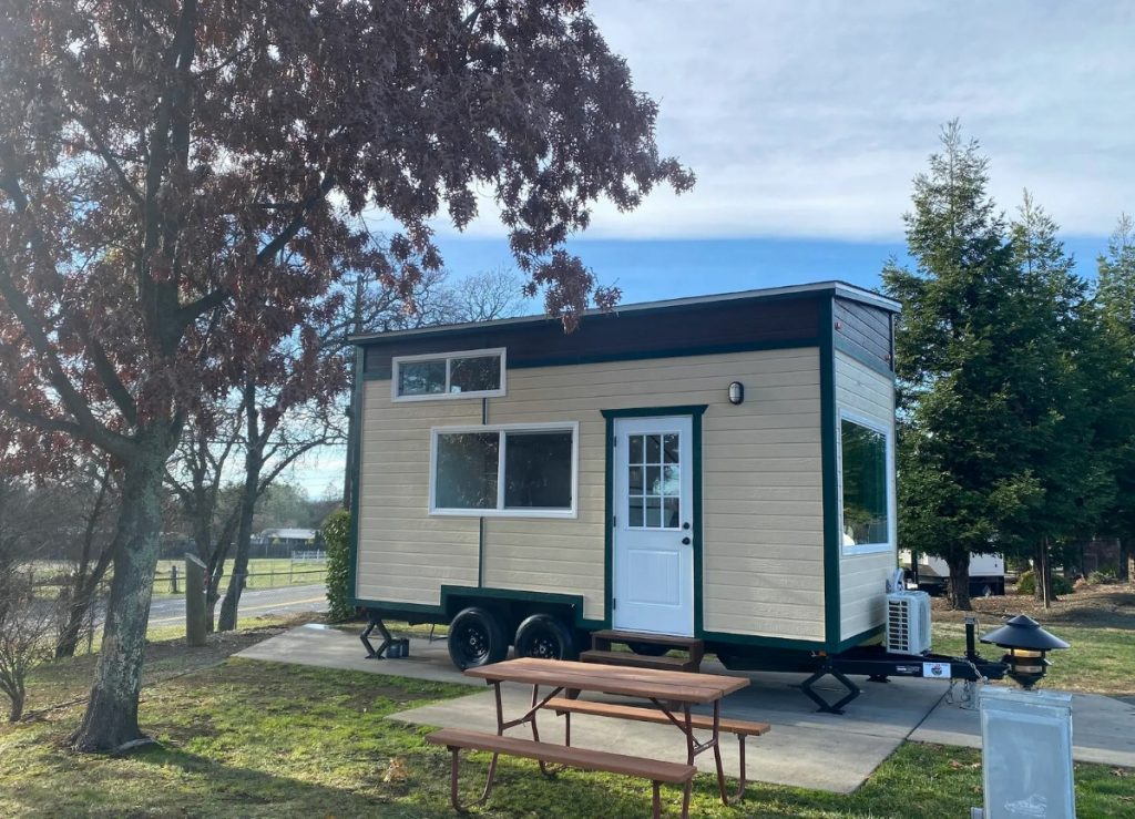 Tan and black tiny house on wheels with white door