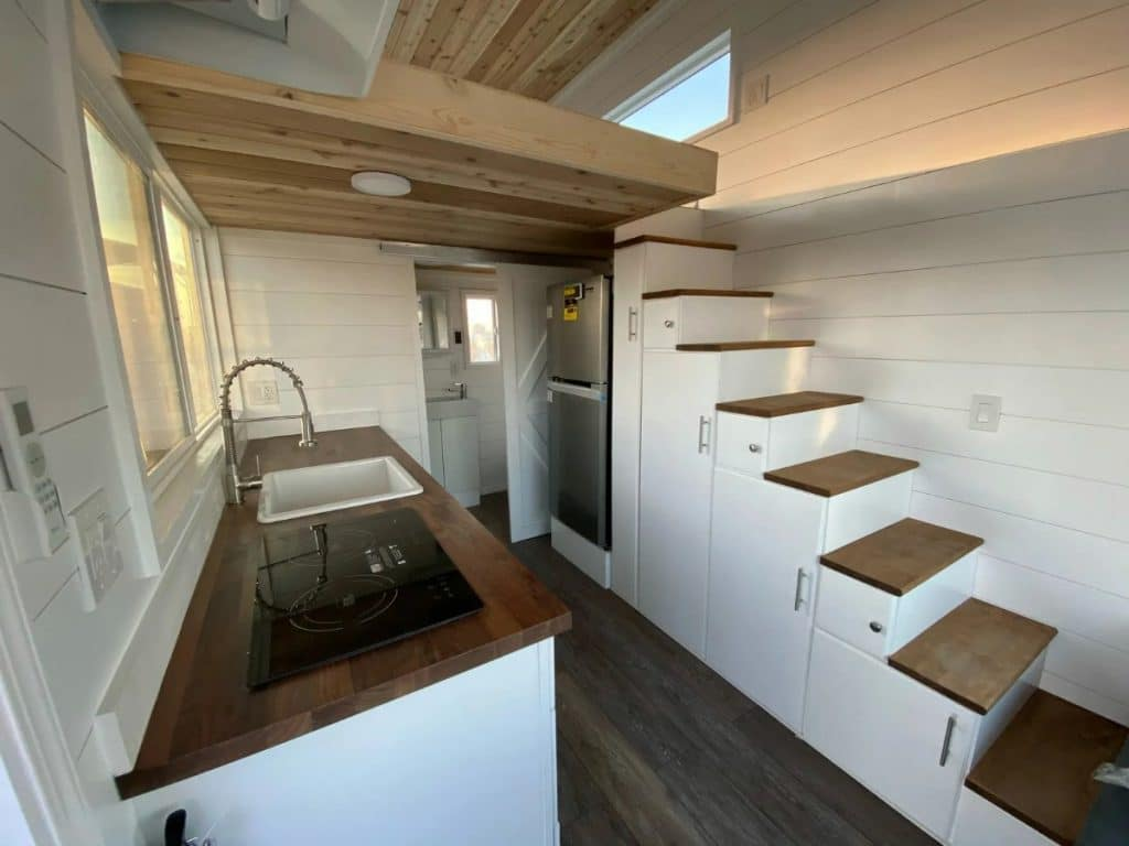 View of tiny kitchen with refrigerator under stairs