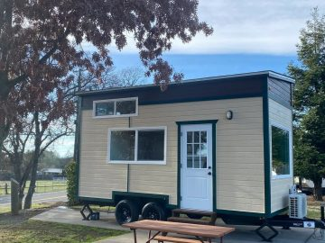 Tan and black tiny house with white door