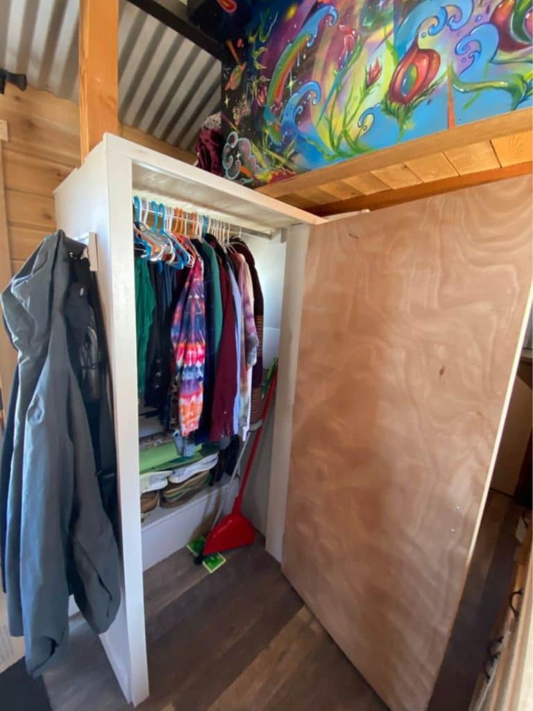 Open tiny closet with white exterior and wooden door