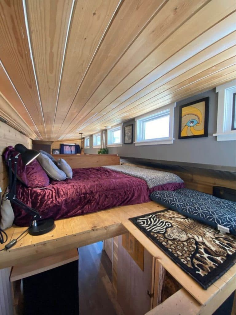 Maroon bedding on large bed in loft of tiny home