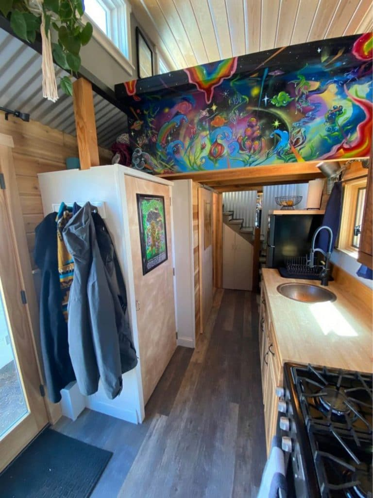 Colorful art above tiny closet with coats on outside