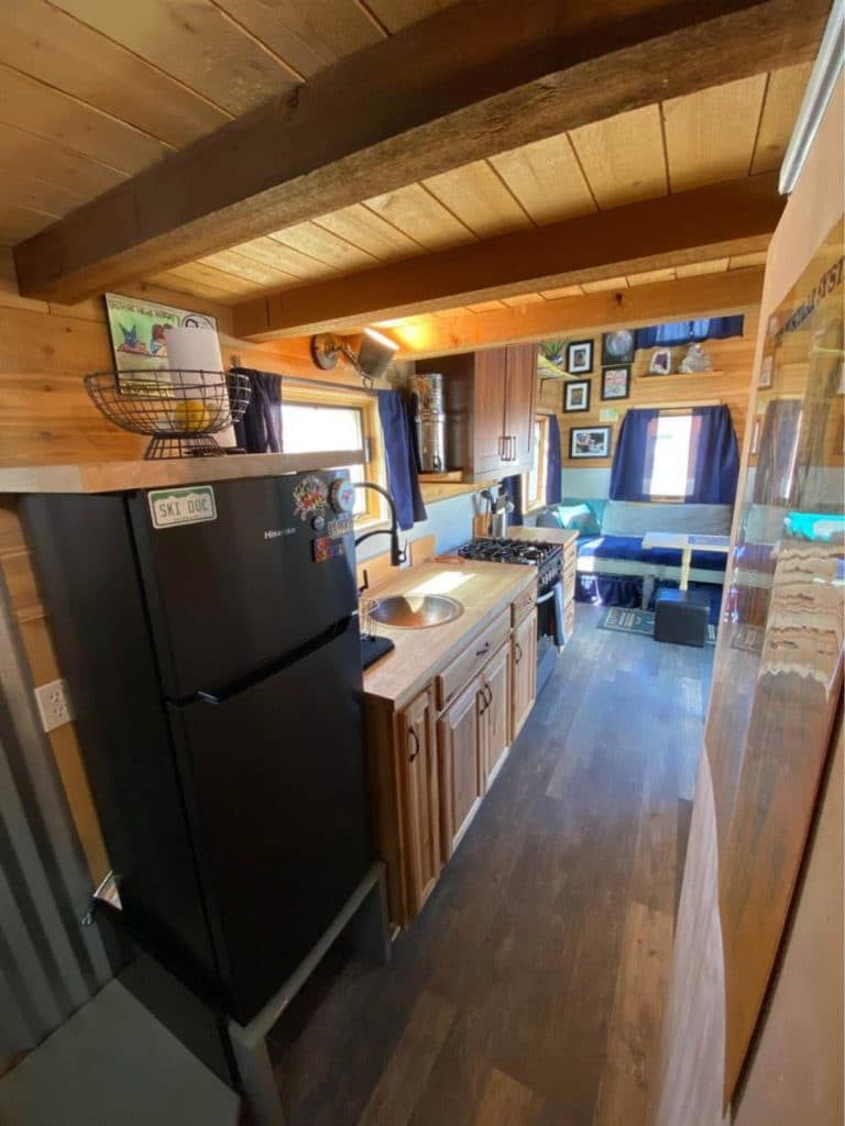 View don length of tiny home showing black refrigerator in foreground