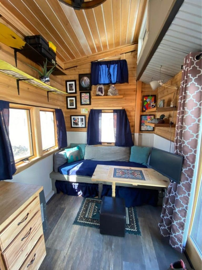 Blonde wood walls, blue couch, and wooden table in tiny living space