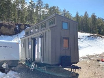 Tiny home parked by snow bank