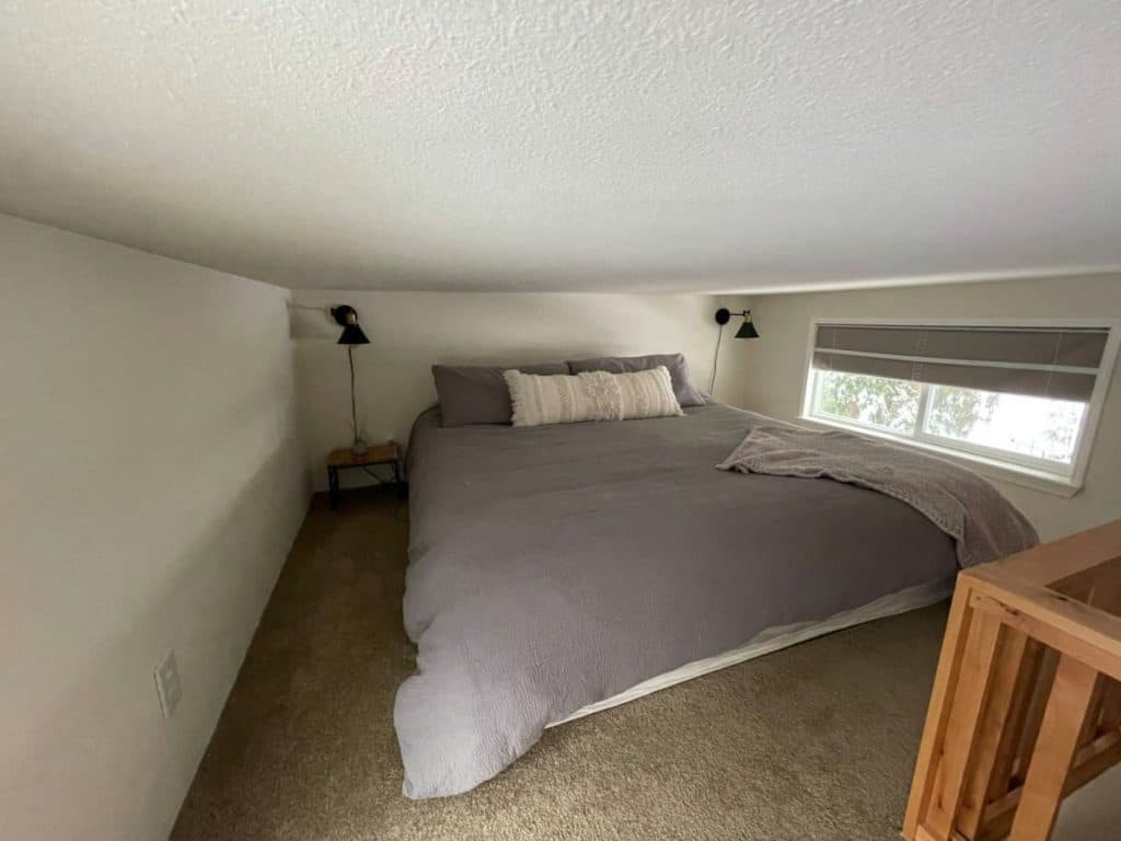 Bed with gray linens in loft next to long window