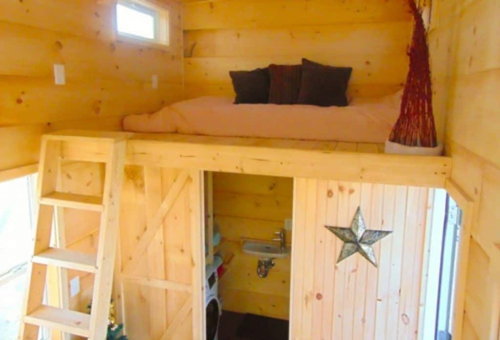 Loft above bathrom with wooden ladder