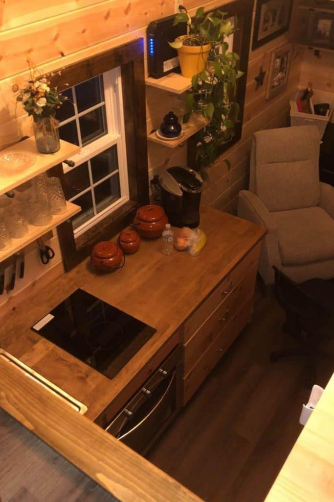View of tiny house kitchen and living area from loft