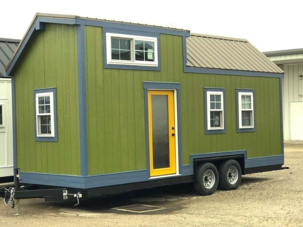 Tiny house on wheels with green siding and blue trim and yellow door