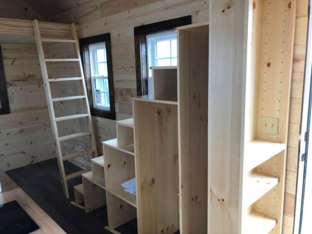 Empty tiny house with raw wood stairs and cabinets